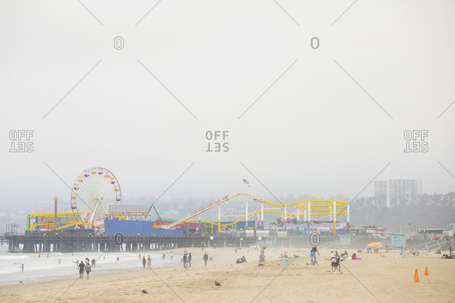 Santa Monica, California - July 22, 2020: Beachgoers enjoying a day on Santa Monica beach with pier in the background