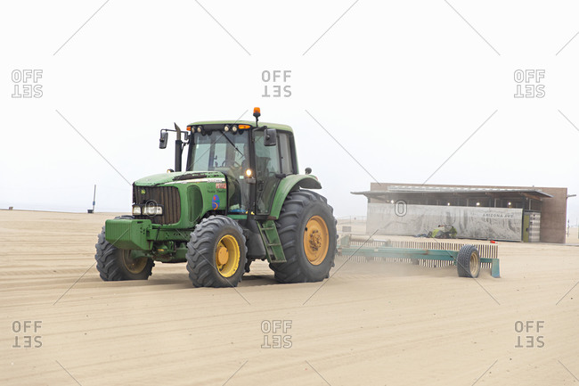 Santa Monica, California - July 22, 2020: A green tractor combing the Santa Monica Beach on a cloudy day