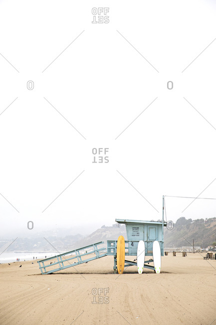Santa Monica, California - July 22, 2020: Surfboards leaning on a blue lifeguard post on the Santa Monica Beach on a cloudy day