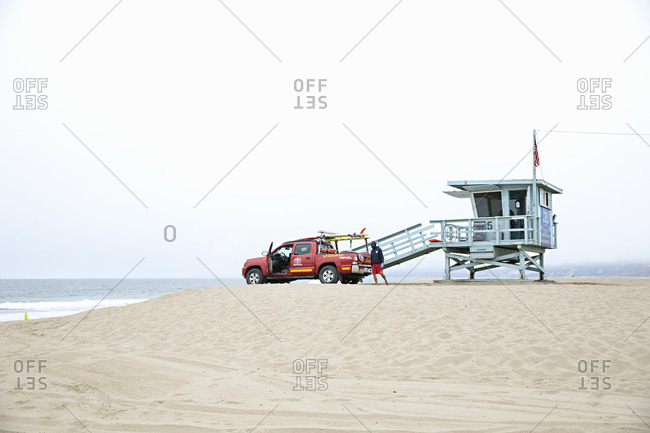 Santa Monica, California - July 22, 2020: Lifeguard in protective gear with red truck on the Santa Monica Beach on a cloudy day
