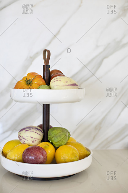 Fresh produce on a two-tier stand on kitchen counter with marble background