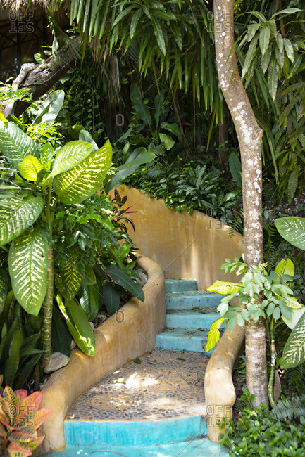 Colorful winding exterior staircase surrounded by tropical foliage