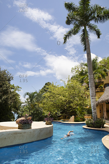 Sayulita, Nayarit, Mexico - June 14, 2018: Tourist swimming in a luxury resort swimming pool