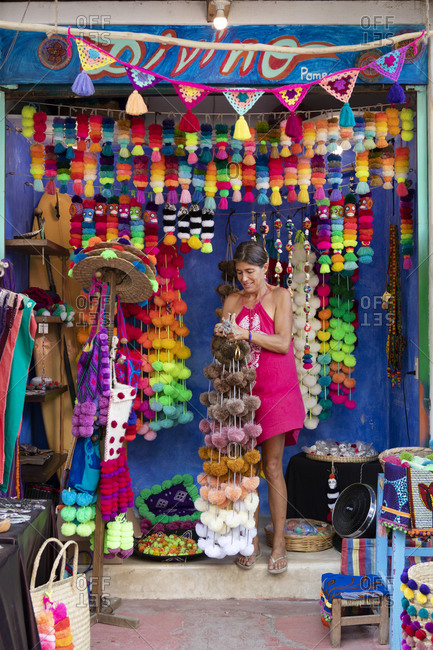 Sayulita, Nayarit, Mexico - June 14, 2018: Woman selling colorful pom-pom garlands her roadside stand