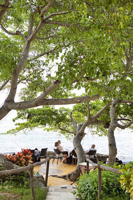 Sayulita, Nayarit, Mexico - June 15, 2018: People enjoying a meal at an oceanside restaurant's outdoor dining area