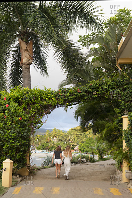 Sayulita, Nayarit, Mexico - June 15, 2018: Rear view of two women walking under vine arch on a street leading to beach