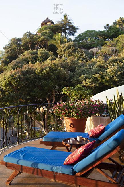 Two lounge chairs with blue cushions on a terrace at sunset in Sayulita, Mexico