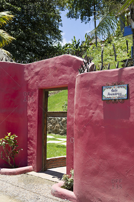 Sayulita, Nayarit, Mexico - June 16, 2018: Red Adobe style wall exterior of hacienda in Sayulita