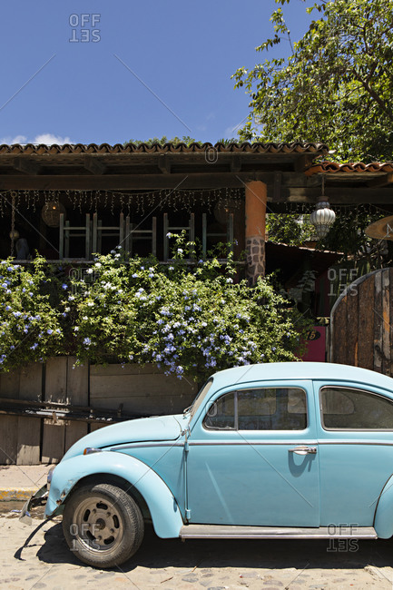 Sayulita, Nayarit, Mexico - June 16, 2018: Vintage blue car parked on street in front of home in Sayulita