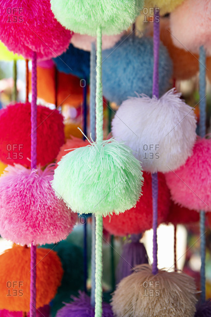 Close up of colorful pom-pom garlands for sale at a shop in Sayulita, Nayarit, Mexico