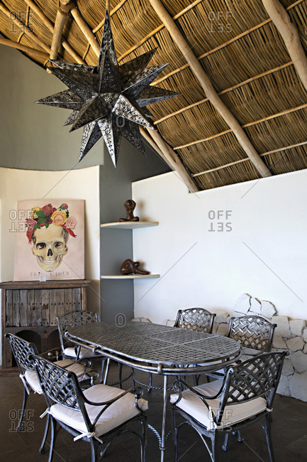Sayulita, Nayarit, Mexico - June 17, 2018: Large star shaped light fixture over dining room interior in a home with vaulted thatched roof