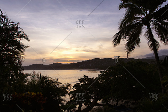 View of a sunset over the Pacific Ocean with palm trees on the coast of Sayulita, Nayarit, Mexico