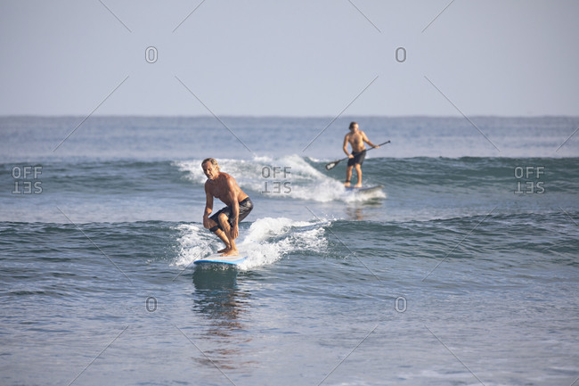 Sayulita, Nayarit, Mexico - June 18, 2018: Surfer and stand up paddleboarder off the Pacific coast of Sayulita
