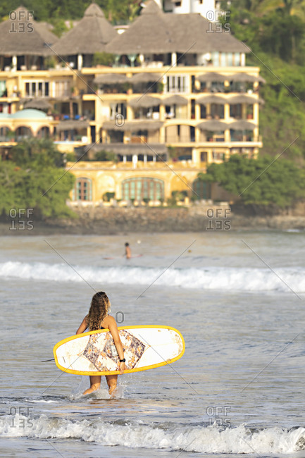 Sayulita, Nayarit, Mexico - June 18, 2018: Young woman carrying surfboard in the waves of the Pacific Ocean