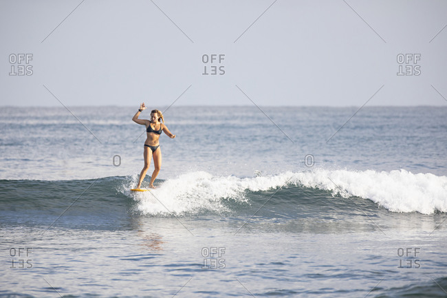 Sayulita, Nayarit, Mexico - June 18, 2018: Young woman riding a wave on her surfboard in the Pacific Ocean