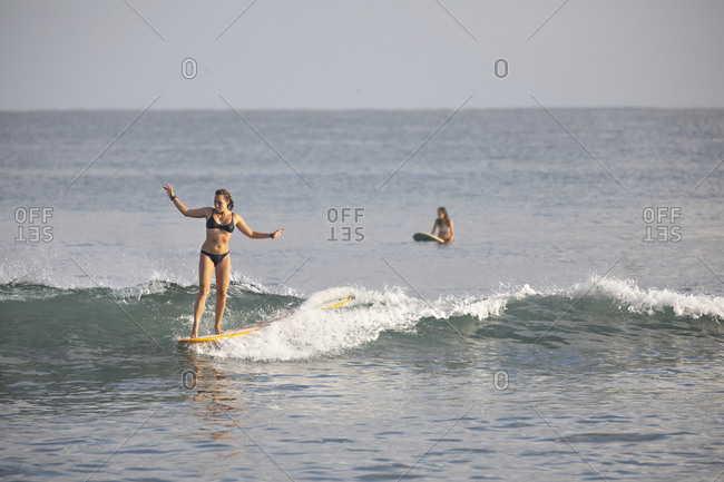 Sayulita, Nayarit, Mexico - June 18, 2018: Young female surfers in the Pacific Ocean off the Mexican coast