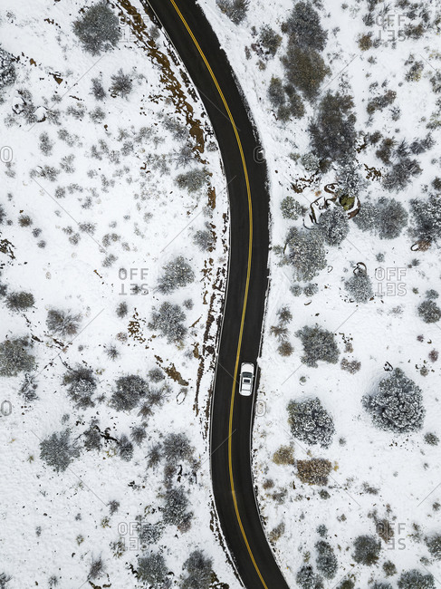 Car Driving on a Winding Road in the Snow at the Sandia Mountains in New Mexico