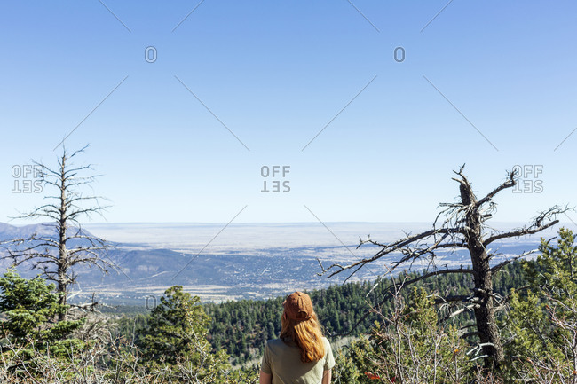 Redhead Woman Looking at the View of the Sandia Mountains in Albuquerque New Mexico