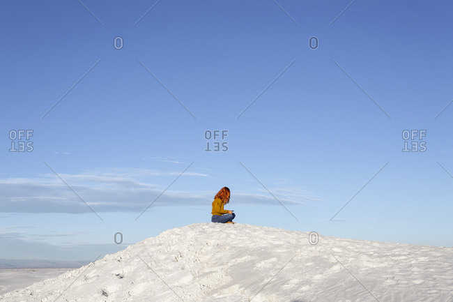 Redhead Woman Sitting on Top of a Sand Dune at White Sands National Monument, New Mexico