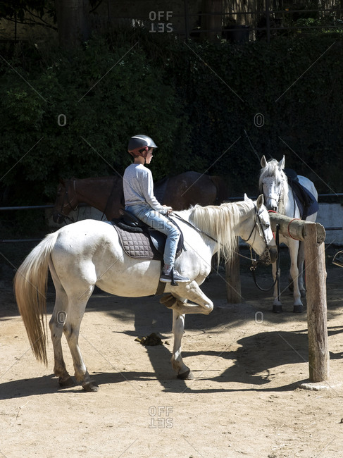 Side view of a young boy riding a little white horse