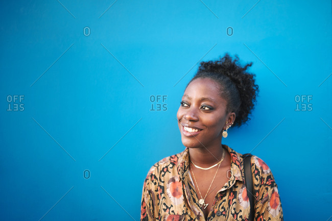 Portrait of young black woman smiling on a blue background with copy space