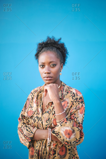 Portrait of young elegant black woman on a blue background with copy space