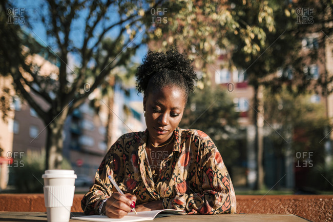 Young black woman writing notes in her agenda sitting in an outdoor cafe