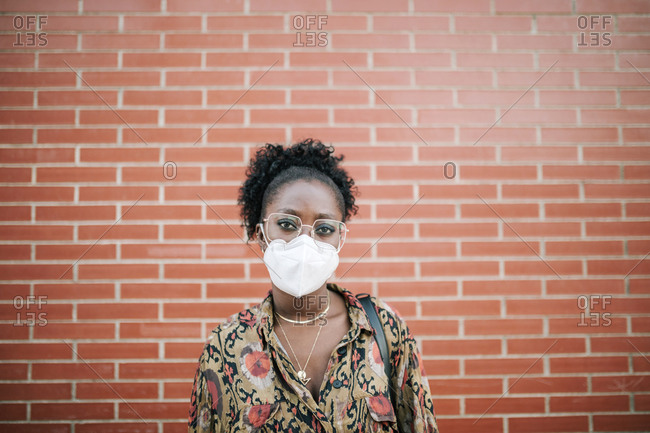 Portrait of young black woman with face mask on brick background