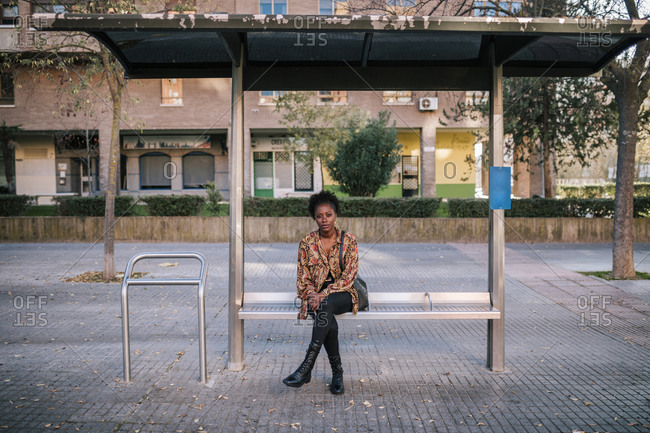 Young black woman sitting waiting for the bus at a city bus stop