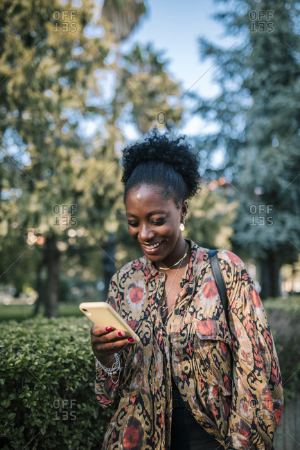 Young black woman typing on her yellow mobile phone in the city