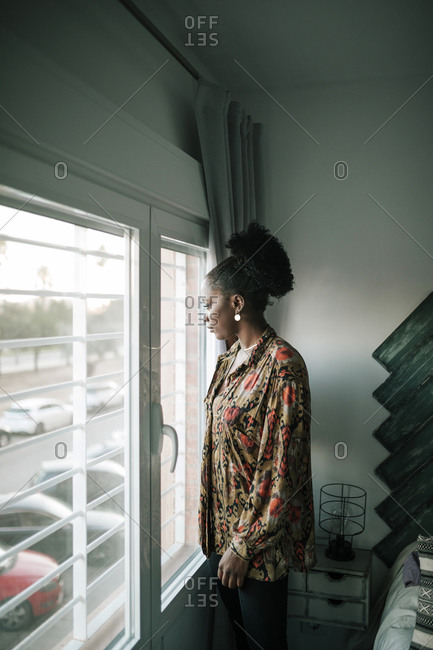 Portrait of young black woman looking out of her bedroom window