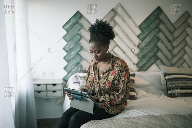 Young black woman with tablet lying on the bed in an apartment