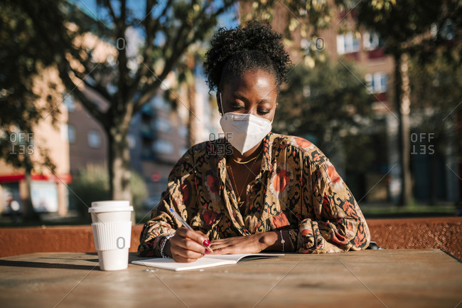 Black woman with face mask writing notes in outdoor cafe