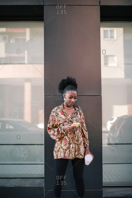 Black woman with mobile phone having coffee in the city