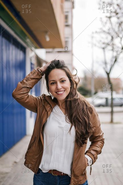 Caucasian young woman walking smiling through the city