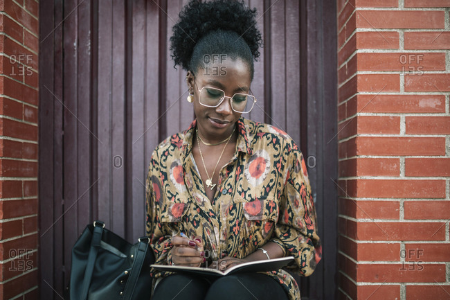 Young black woman writing in her agenda in the city
