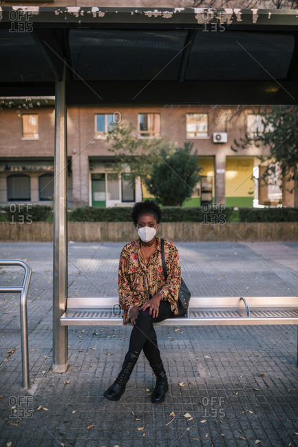 Black woman with mask sitting alone at bus stop