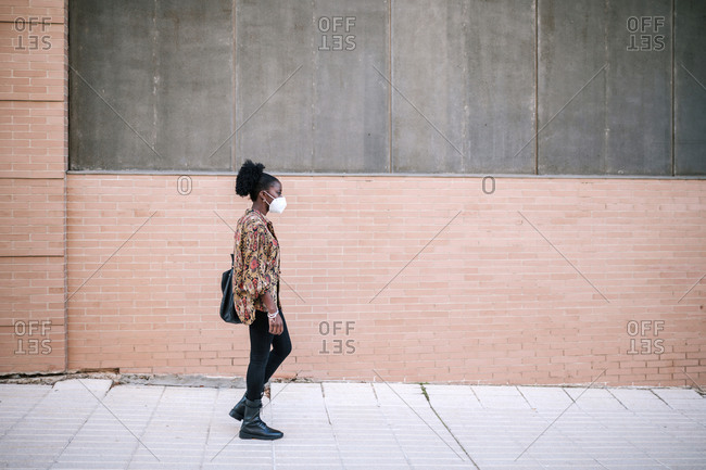 Black woman with mask walking down the street