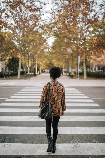 Elegant black young woman crossing crosswalk