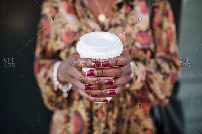 Young black woman with coffee in the city