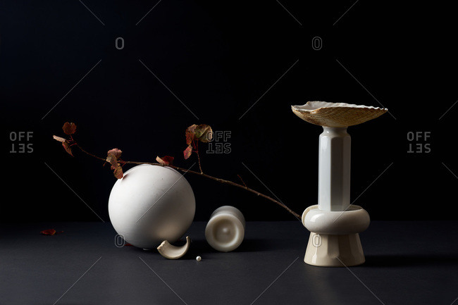 Still life with white sphere, dried plant and white objects on dark background