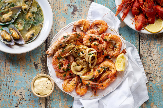 Top view of grilled seafood platter with shrimps, cooked crawfish and a plate of steamed kiwi mussels with parsley served with lemon wedges