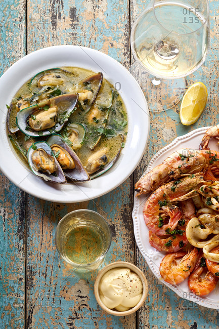 Grilled seafood platter with shrimps, kiwi mussels and a plate of steamed green mussels with parsley served with lemon wedges