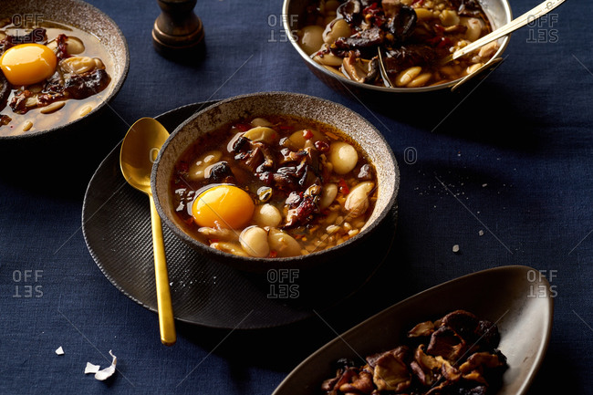 Hot stew with lima beans, shiitake mushrooms, farro and egg yolk.