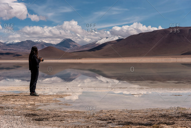 Woman with a camera photographing a volcano in the southwest of the altiplano in Bolivia