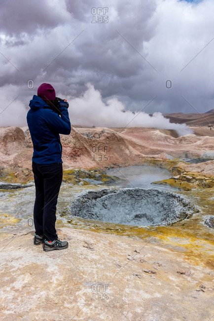 Woman with a camera photographing some mud pits with volcanic activity in the Andean Highlands, Bolivia.