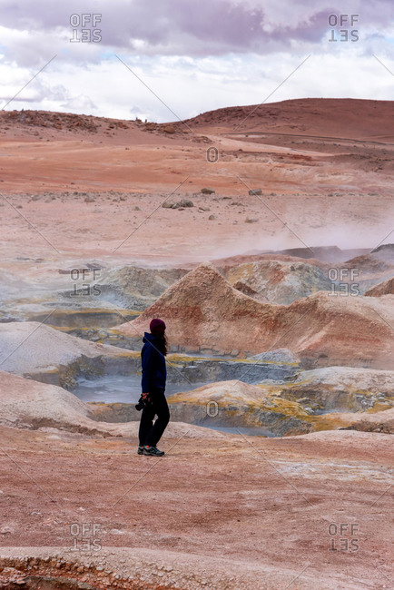Woman with a camera walking through some mud pits with volcanic activity in the Andean Highlands, Bolivia.