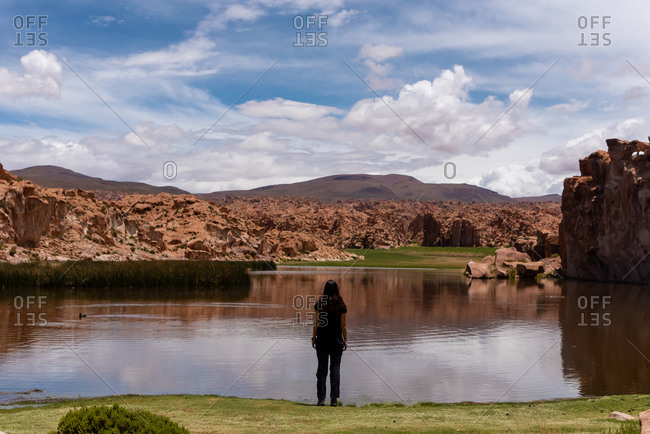 Back view of a woman in front of a scenic lake in the southwest of the Bolivian altiplano
