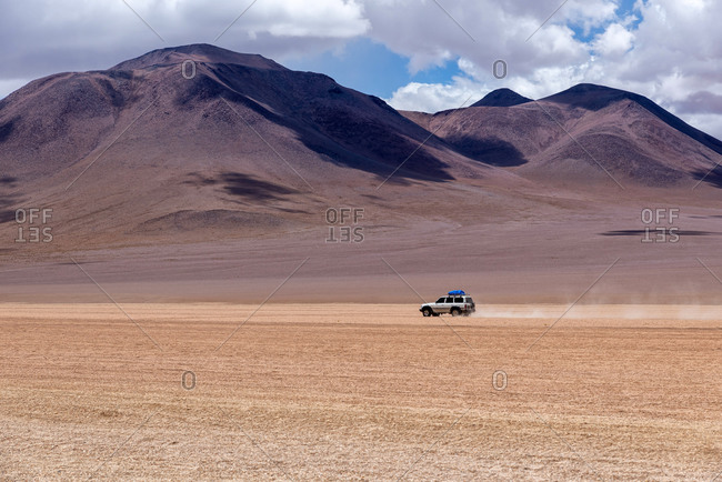 A 4x4 driving through the southwest of the altiplano in Bolivia in a cloudy day