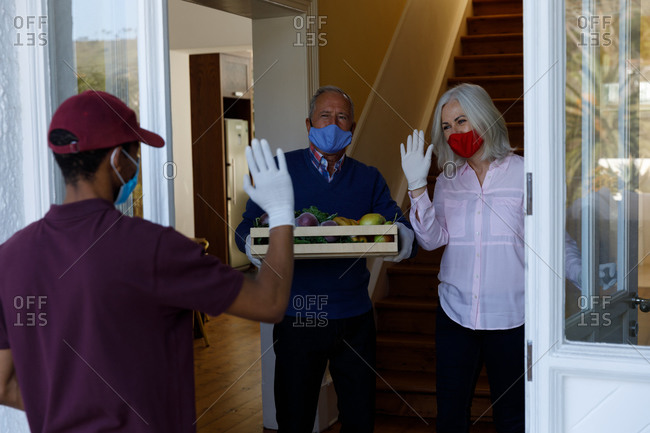 Delivery man wearing face mask delivering groceries to senior caucasian couple wearing face mask at